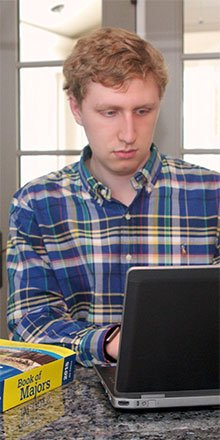 Student researching colleges on laptop